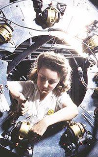 Woman reviewing the cowling of one of the motors of a B-25 bomber